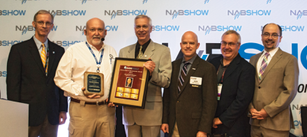 Wayne Pecena (second from left) receives a plaque from Radio World Editor-in-Chief Paul McLane (far right) at the 2015 Ennes Workshop at the NAB Show.
